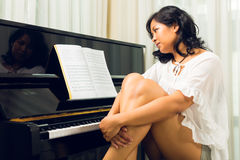 Asian woman sitting at the piano Royalty Free Stock Images