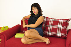 Asian woman sitting on red sofa Stock Images