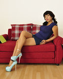 Asian woman sitting on red sofa legs crossed Stock Image