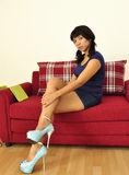 Asian woman sitting on red sofa legs crossed Royalty Free Stock Image