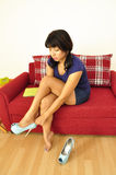 Asian woman sitting on red sofa putting her shoes on Royalty Free Stock Photography