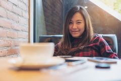 Asian woman sitting and relax in modern cafe with coffee cup , smart phone and wooden table foreground. A smiley beautiful Asian woman sitting and relax in Stock Images
