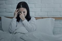 Asian woman sitting and sad on bed stock image