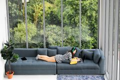 Asian woman sitting and selfie on sofa near big glass windows,. Relaxing alone in house with green forest in background stock photo