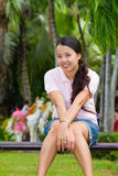 Asian woman sitting and smile on bench Stock Images