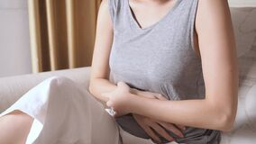 Asian woman sitting on sofa in living room with stomach ache. female belly pain due to pregnancy.