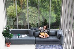 Asian woman sitting on sofa near big glass windows, relaxing alo royalty free stock photo