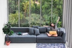 Asian woman sitting on sofa near big glass windows, relaxing alone in house with green forest in background. Asian woman sitting on sofa near big glass windows royalty free stock photography