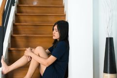 Asian woman sitting on stairs with depression of lonely have a headache,Mental disorder health care concept stock photos