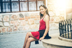 Asian woman sitting on Stone bench in city. Portrait of Asia young pretty girl in park royalty free stock photo
