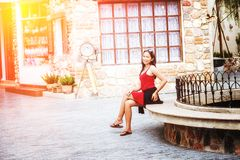 Asian woman sitting on Stone bench in city. Portrait of Asia young pretty girl in park royalty free stock photography