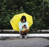 Asian woman sitting using mobile phone under umbrella Royalty Free Stock Photo