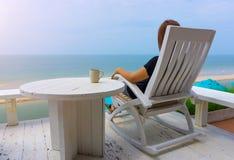 Asian woman sitting on white wood beach chair Stock Photo