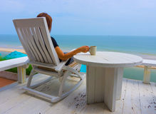 Asian woman sitting on white wood beach chair Royalty Free Stock Photo