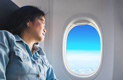 Asian Woman sitting at window seat in airplane and look outside. Window see blue sky and cloud ,traveling concept Royalty Free Stock Images