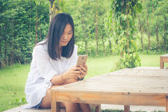 Asian woman sitting on wooden chair at outdoor garden and playing her smartphone. Autumn filter effect Stock Image