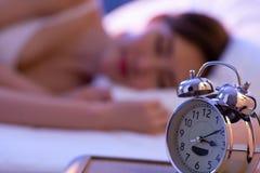 Asian woman sleep with clock stock photos