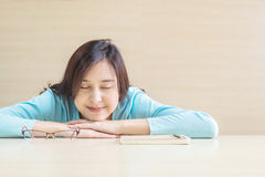 Asian woman sleep by lied on desk with happy face in rest time from reading book on blurred wooden desk and wall textured backgrou Stock Photo