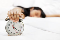 Asian Woman Sleeping on bed. Lazy woman sleeping with hand covering an alarm clock in front Royalty Free Stock Photos
