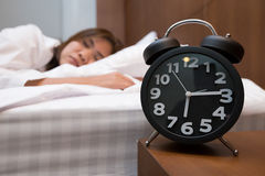 Asian woman sleeping in bed and alarm clock. In home Royalty Free Stock Images