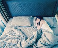 Asian woman sleeping on bed with blanket, top view.  Stock Images