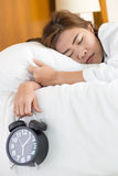 Asian woman sleeping on bed and wake up with alarm clock Royalty Free Stock Image