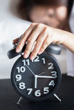 Asian woman sleeping on bed and wake up with alarm clock Stock Photography