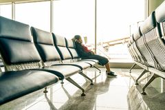 Asian woman sleeping on bench in airport terminal. And waiting for the delayed flight stock image