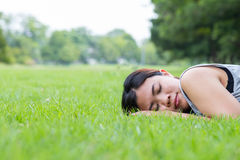 Asian woman sleeping on grass in the park Stock Photo