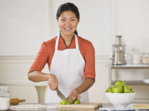 Asian woman slicing apples. Smiling Asian woman standing at counter and slicing apples.Horizontal Stock Photo