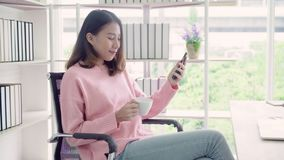 Asian woman in smart casual wear using smartphone and drinking warm cup of coffee while sitting on table in creative office. stock footage
