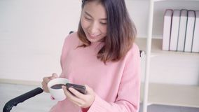 Asian woman in smart casual wear using smartphone and drinking warm cup of coffee while sitting on table in creative office. stock video footage