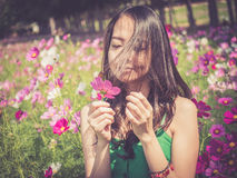 Asian woman smelling a cosmos flower Royalty Free Stock Photo