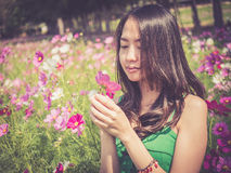 Asian woman smelling a cosmos flower Stock Image