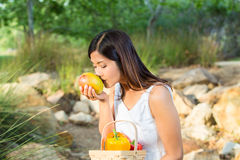 Asian woman smelling a mango while holding a basket of bell peppers and mango Stock Images