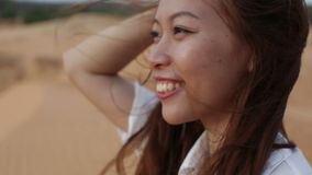 Asian woman smile outdoor desert wind blowing hair. Profile side view close up face of young happy girl stock video footage