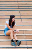 An asian woman smile and sit on the staircase Royalty Free Stock Images