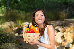 Asian woman smiling with basket of bell peppers and mango Stock Photos