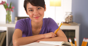Asian woman smiling at desk with books Royalty Free Stock Photos