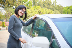 Asian woman with smiling face open passenger car with a vehicle Stock Image