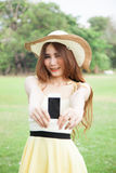 Asian woman smiling and handing a mobile phone. Royalty Free Stock Images