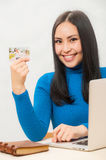 Asian woman smiling and holding her credit card. Stock Images