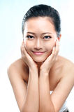 Asian woman smiling holding her head royalty free stock image
