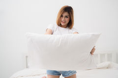 Asian woman smiling and holding white pillow at bedroo Stock Photography