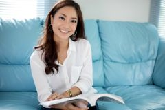 Asian women smiling and reading a book for relaxation at home Stock Image