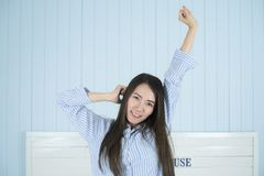 Asian woman smiling and stretching in the morning at bedroom after waking up. Beautiful young asian woman smiling and stretching in the morning at bedroom after Royalty Free Stock Images