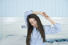 Asian woman smiling and stretching in the morning at bedroom after waking up. Beautiful young asian woman smiling and stretching in the morning at bedroom after Stock Image