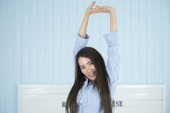 Asian woman smiling and stretching in the morning at bedroom after waking up. Beautiful young asian woman smiling and stretching in the morning at bedroom after Royalty Free Stock Photo