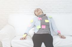 Yellow, green and pink paper sheets On the woman who is sleeping And exhausted from work. royalty free stock image