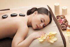 Asian woman in spa with hot stones. Health and beauty, resort and relaxation concept - asian woman in spa salon getting massage with hot stones Royalty Free Stock Photos